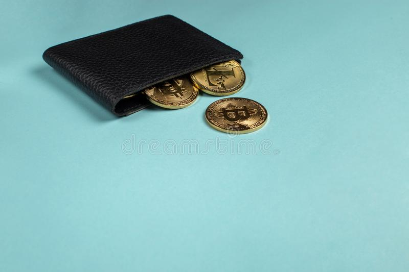 Crypto-currency in the physical purse. The concept of virtual money in the wallet. On a blue background. Copyspace stock images