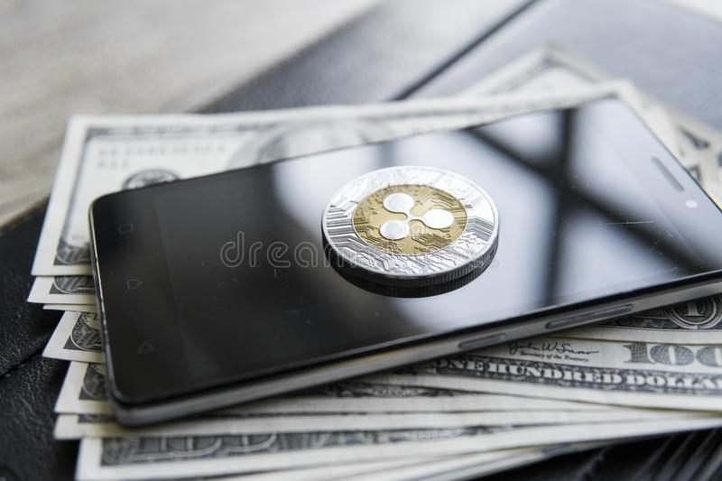 Crypto currency ripple xrp on smartphone and us dollars money background. Blockchain and cyber currency. Global money. Exchange, bussiness, commercial. Cash stock image