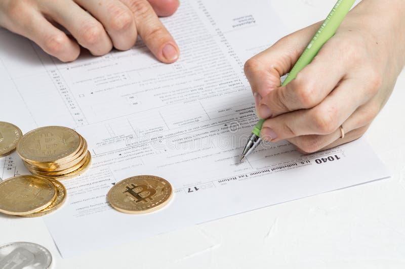 Crypto-monedas: rellenando el impreso 1040 de impuesto para pagar impuestos sobre renta de operaciones con crypto-moneda foto de archivo