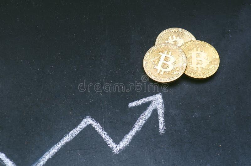 Crypto muntconcept Bitcoin gouden muntstukken op een bord met handelsgrafiek Beweging op tendens Virtuele munt nieuw virtueel gel royalty-vrije stock foto