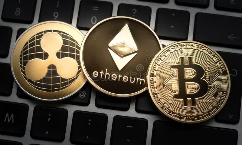Cryptocurrencies Ethereum, krusnings- och Bitcoin mynt på datorbärbar datortangentbordet royaltyfri fotografi