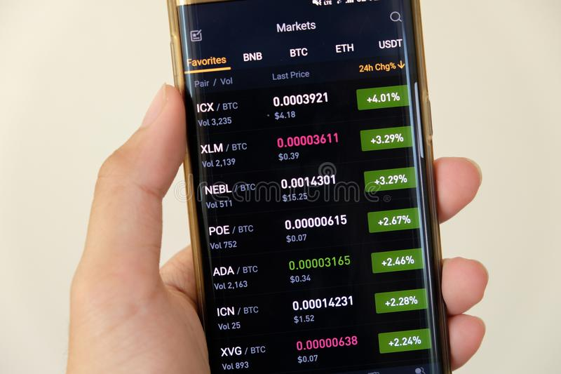 Cryptocurrency市场在智能手机的图表屏幕买卖按钮和手有迷离背景 Blockchain, Fintech 免版税库存图片