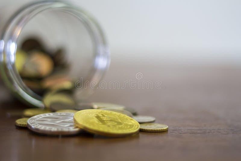Cryptocurrency硬币,Bitcoin和Litecoin,从一个玻璃瓶子溢出 库存图片