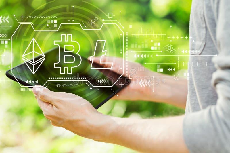 Cryptocurrency - Bitcoin, Ethereum, Litecoin avec l'homme tenant son comprimé photos stock