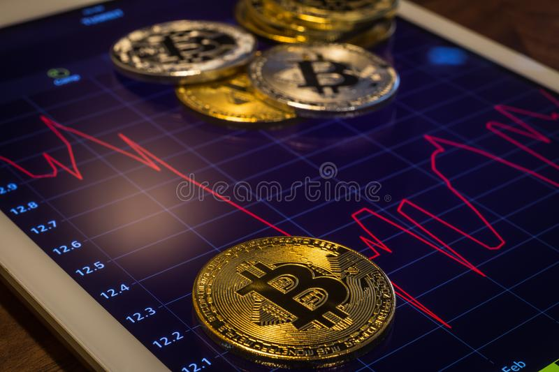 Cryptocurrency bitcoins on screen show price drop graph. Cryptocurrency gold silver metal, focus on bitcoin sign, coins put on modern tablet screen that showing royalty free stock images