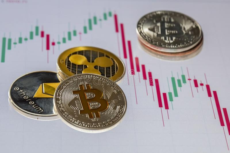 Cryptocurrency coins over trading candles graphic screen; Bitcoin, Ethereum and Ripple coins royalty free stock photos