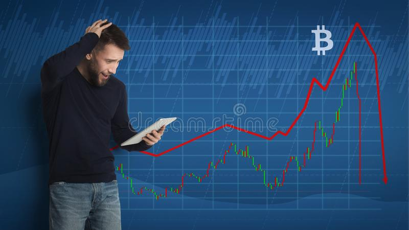 Surprised young man watching bitcoin drop stock photography
