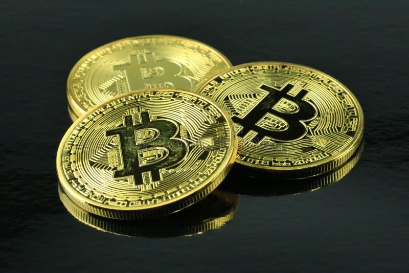 Cryptocurrency di tre Bitcoins su un fondo nero immagini stock libere da diritti
