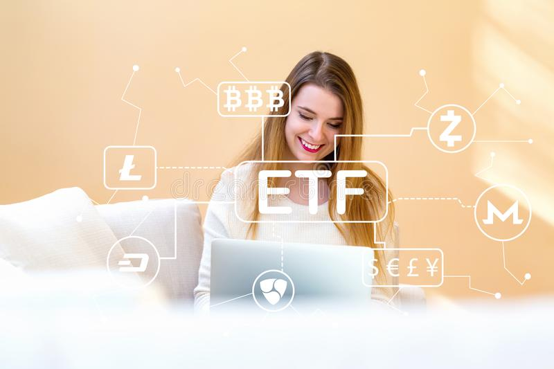 Cryptocurrency ETF theme with young woman using her laptop. Computer at home stock photo