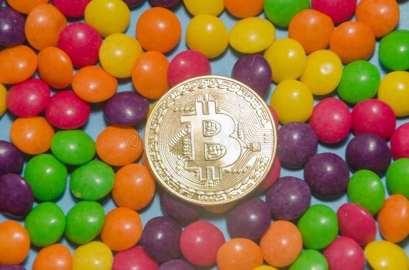 Cryptocurrency-Gold-bitcoin liegt auf Süßigkeit, Karamell lizenzfreie stockbilder