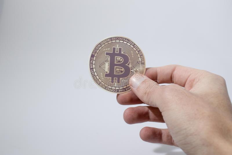 Cryptocurrency, hand holds a bitcoin in a white background stock photography