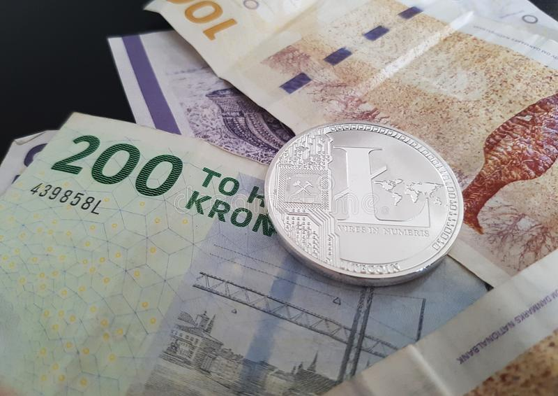 Cryptocurrency Litecoin LTC, das auf eine Geldwährungspapier-Rechnungsoberfläche legt stockbild