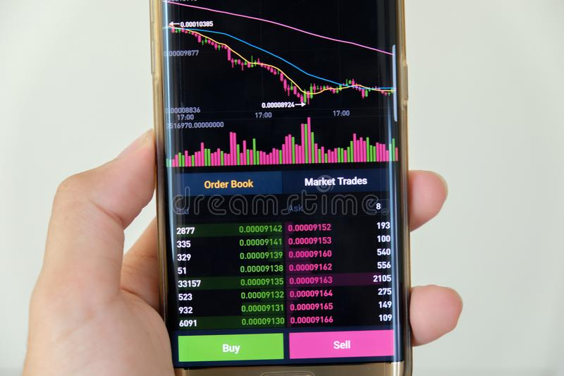Date StampCryptocurrency market graph screen on smartphone buy and sell button and hand with blur background. Blockchain , Fintech. Cryptocurrency market graph royalty free stock images