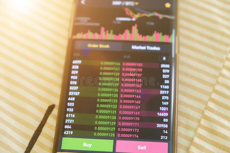 Date StampCryptocurrency market graph screen on smartphone buy and sell button and hand with blur background. Blockchain , Fintech. Cryptocurrency market graph stock photo