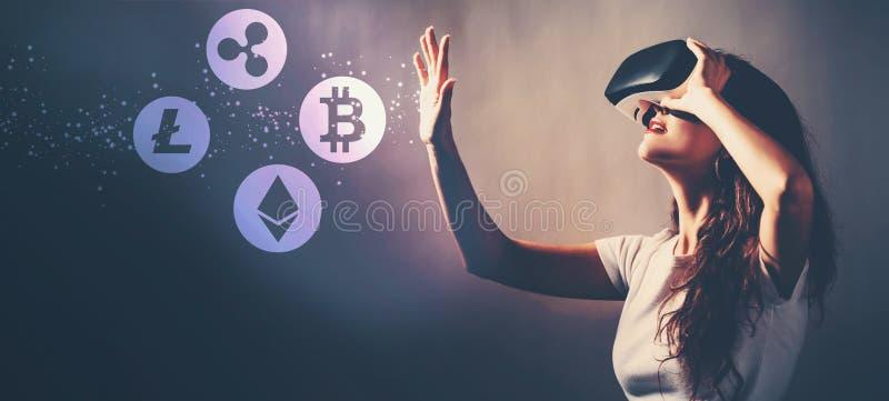 Cryptocurrency med kvinnan som använder en virtuell verklighethörlurar med mikrofon royaltyfri fotografi