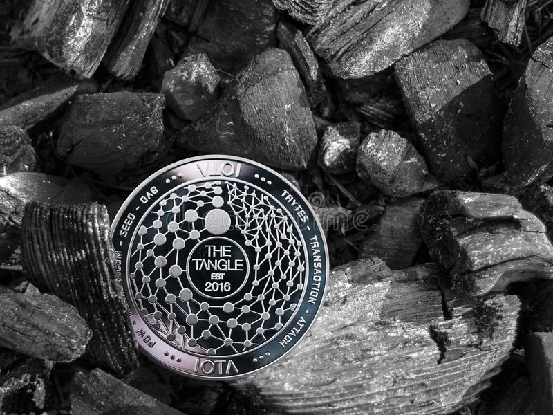 Cryptocurrency MIOTA coin lies on coal. Mining and Energy for mining. stock photography