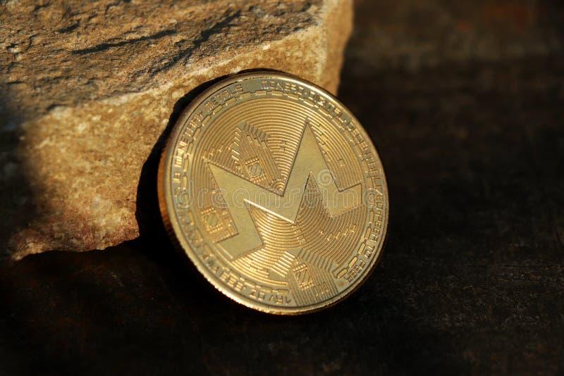 Cryptocurrency, moneta, roccia e legno In mezzo all'immagine una bella moneta famosa come monero fotografia stock