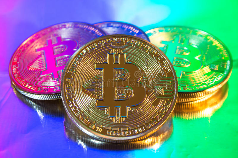 Cryptocurrency physical golden bitcoin coin on colorful background stock photos