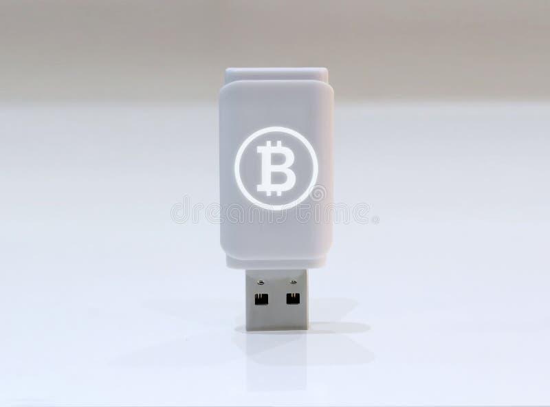Cryptocurrency privat tangent med den glödande Bitcoin logoen - USB pråligt drev på vit yttersida arkivbilder