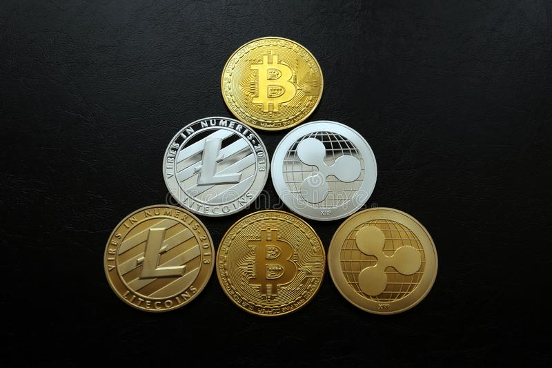 A pyramid of crypto currencies Bitcoin Ripple Litecoin. Cryptocurrency, a pyramid of gold and silver Bitcoins, Ripples and Litecoins on a black leather texture stock image