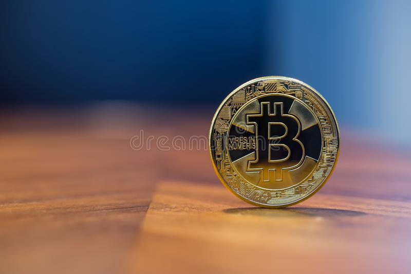 Cryptocurrency sign silver Bitcoin with blue background. Cryptocurrency symbol sign, focus on gold metal Bitcoin stack on wooden table, blur dark blue wall stock photos