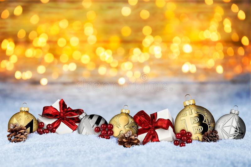 Cryptocurrency xmas background crypto coin christmas bauble ball. S and gifts in snow in front of warm lights bokeh snow texture stock photo