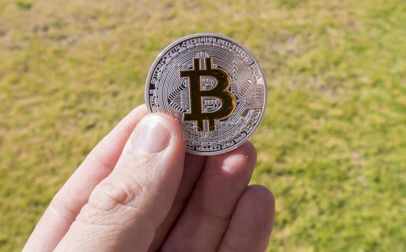 Cryptocurrencymuntstukken in een hand; Bitcoin stock foto
