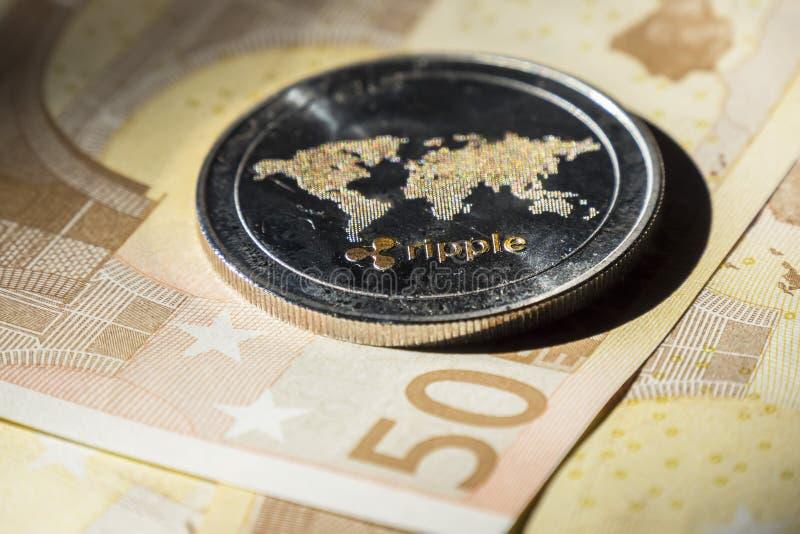 Cryptocurrencymuntstukken over euro bankbiljetten; Rimpelingsmuntstuk stock foto