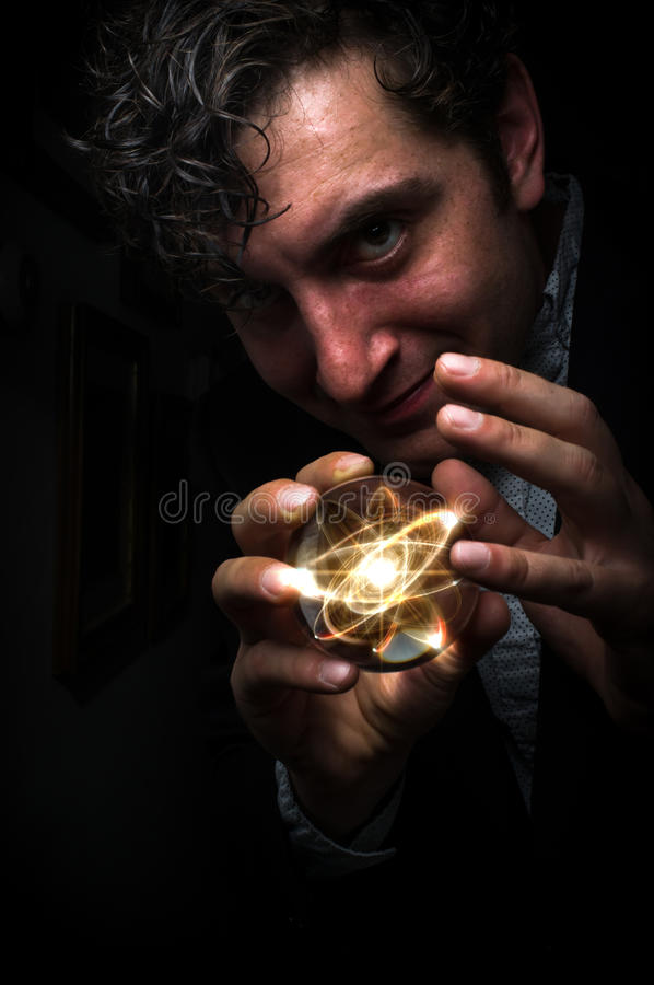Crystal Ball Atom. Holding atom in fortune teller magic crystal ball royalty free stock photography