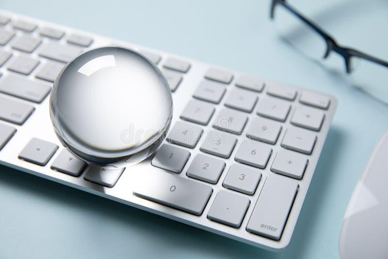 Crystal ball on computer keyboard. Crystal ball on white computer keyboard stock photography