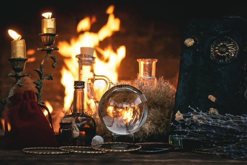 Crystal ball. Crystal ball, magic book, magic potion and other wizard accessories on a table on a burning fire background, spell, reading, future, divination stock photo