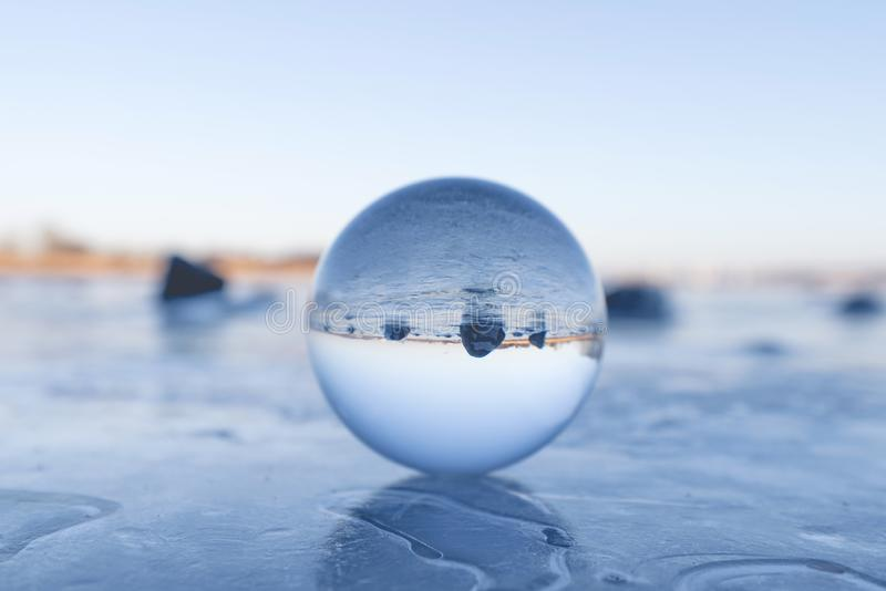 Crystal ball on a frozen lake in the winter royalty free stock photos