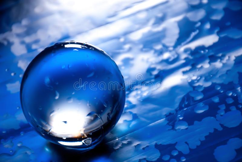 Glass ball in abstract blue with water drops reflections. stock images
