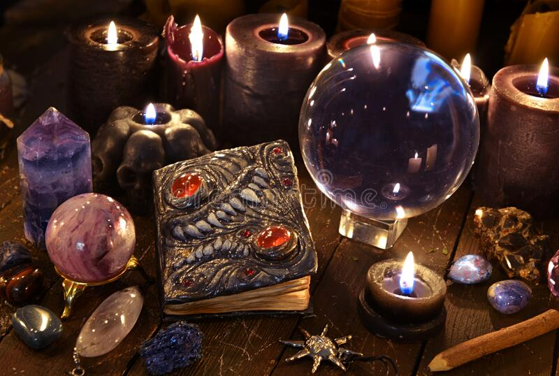 Crystal ball, magic book and burning black candles on witch table royalty free stock image