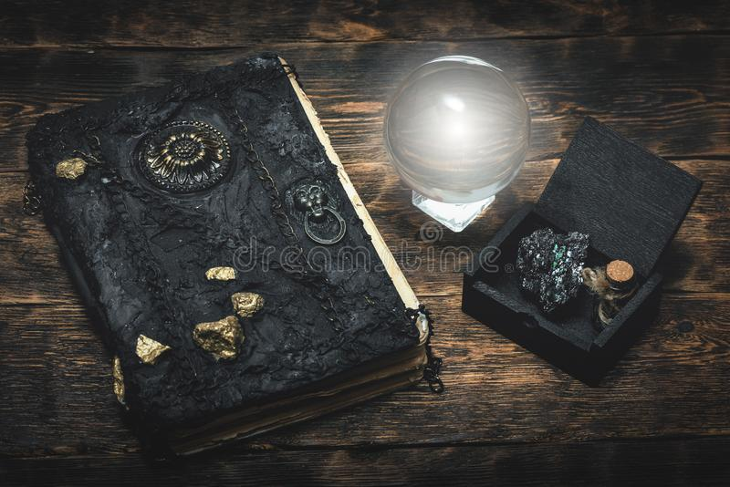 Crystal ball and magic book. Crystal ball and a magic book on a wizard table background stock images