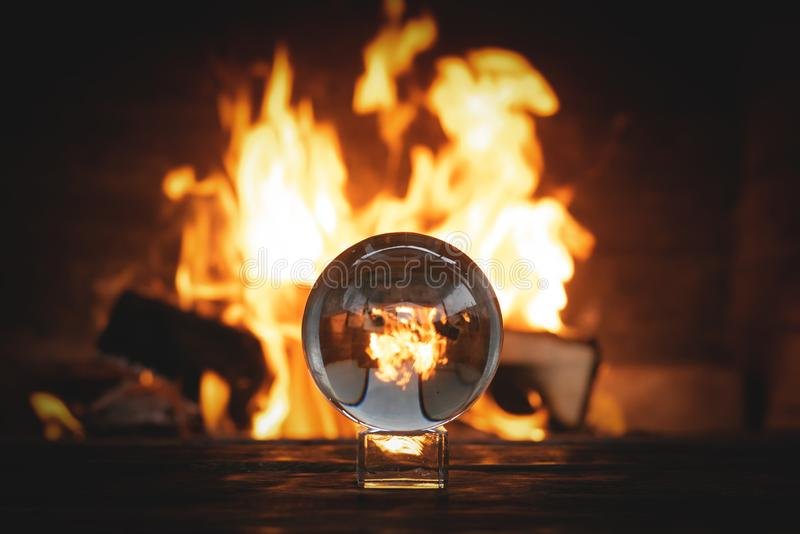 Crystal ball. Crystal ball on the magic table on a burning fire background. Future reading, divination, fortune, bonfire, flame, teller, forerunner, spirit stock photography