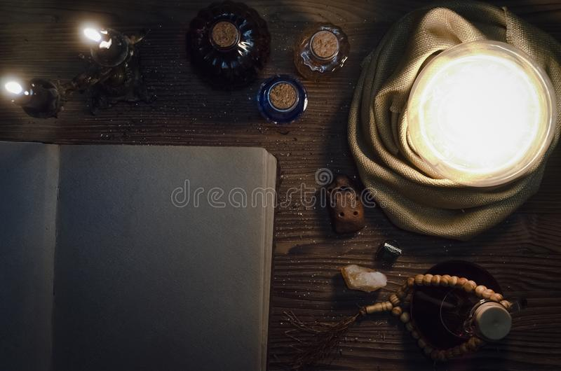 Crystal ball and ancient magic book with copy space. Seance. Future reading concept. Crystal ball and open magic book with blank pages on fortune teller magic stock photography