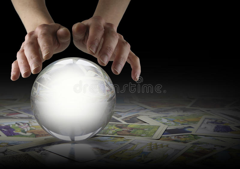 Crystal Ball Reading and Tarot Cards. Hands hovering over a large clear Crystal Ball on a dark background with tarot cards scattered randomly beneath and copy royalty free stock photography
