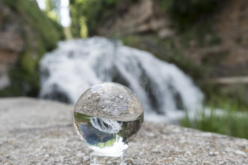Crystal ball reflecting a waterfall. Waterfall reflected on a crystal ball in full spring stock photos