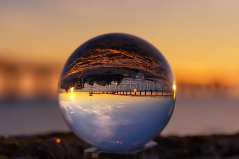 Crystal Ball Reflection on the seashore in sunrise light. Reflection of a bridge in the crystal ball stock images