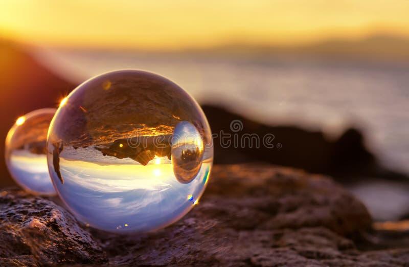 Crystal Ball Reflection sur le bord de la mer dans la lumière de lever de soleil Réflexions de miroir dans des deux boules de cri photo stock