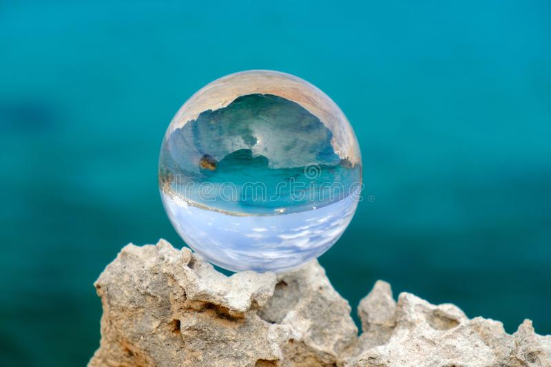 Crystal ball on the rock. On the blue defocused water background. Symbol of summer and vacation on the sea, glass, stone, closeup, close-up, object, ocean royalty free stock image