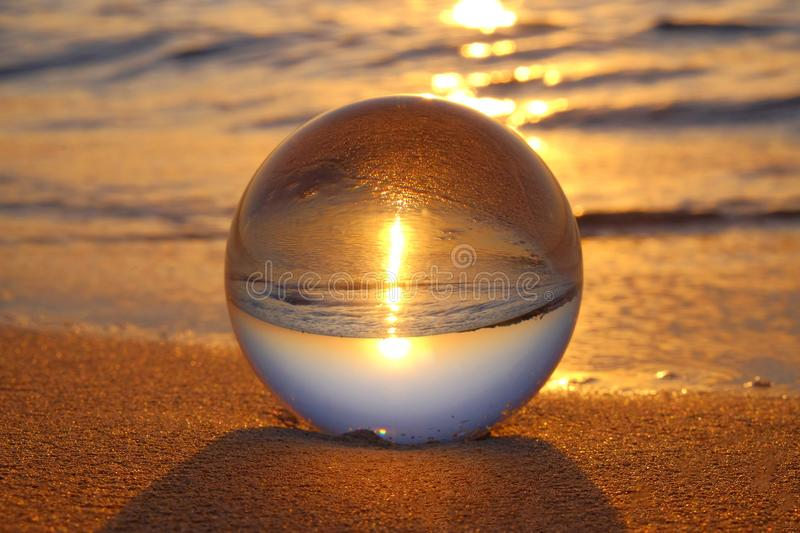 Crystal ball on the sand on the beach at sunset. Beautiful crystal ball on the sand on the beach with sea on the background on the sunset, glass, closeup, close royalty free stock photography