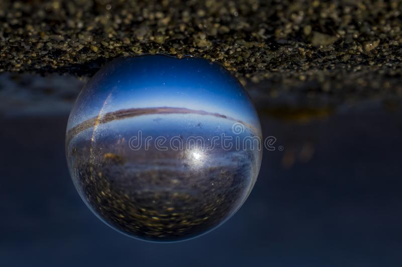 Crystal ball, on sandy beach with lake in background. Crystal Ball Photography. Sandy beach with blue lake and sky in background royalty free stock photo