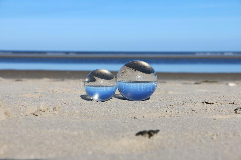 Crystal balls at the beach. Two cystal balls are lying in the sand at the beach royalty free stock image