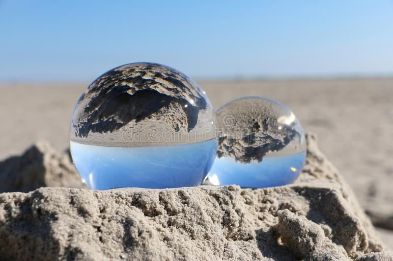 Crystal balls at the beach. Two cystal balls are lying in the sand at the beach royalty free stock photo