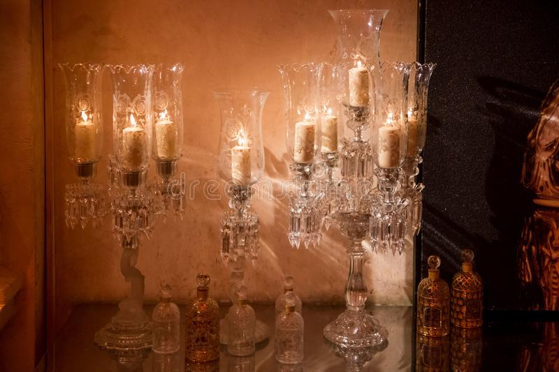 Crystal candlesticks with candles in the form of wine glasses stock image