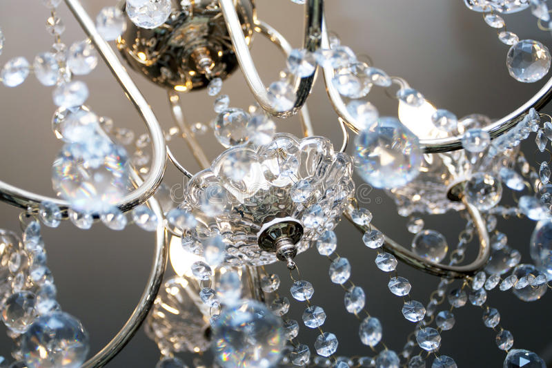 Crystal chandelier. With the included bulbs against a wall royalty free stock image