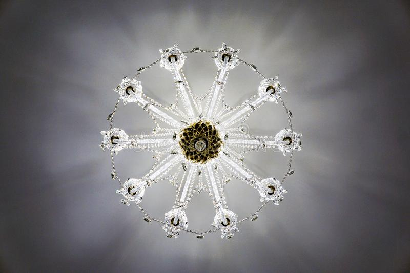 Crystal chandelier on the ceiling, view vertically from the bottom up, pattern, snowflake. Crystal in the interior, the glass elements of the chandelier gives a royalty free stock image