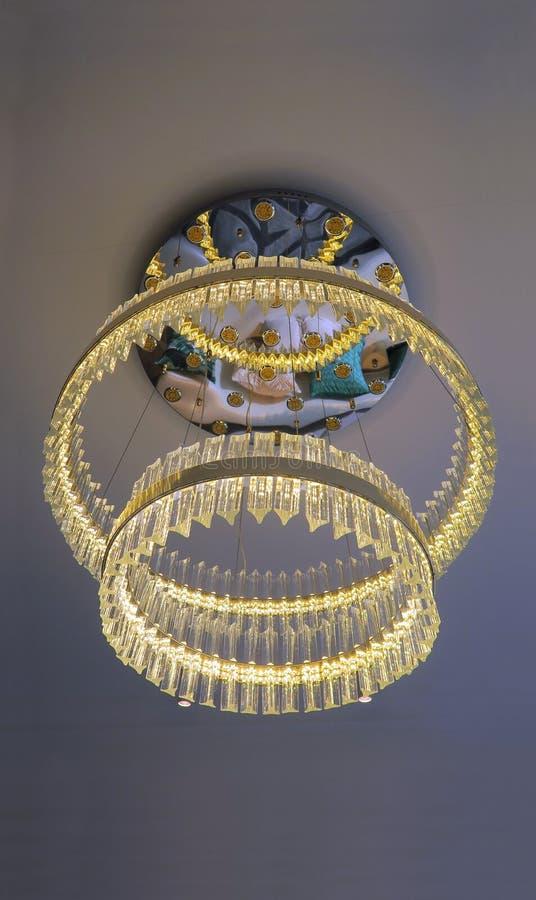 Crystal Chandelier-het hangen onder een plafond met bezinning royalty-vrije stock afbeelding
